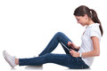Casual woman on floor with tablet side view of a young layed the and playing her isolated white background Royalty Free Stock Photo