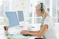 Casual woman with headset using computer in office Royalty Free Stock Images