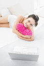 Casual woman with heart shaped pillow and laptop in bed