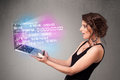 Casual woman holding laptop with exploding data and numers Royalty Free Stock Photo