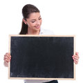 Casual woman looking at blackboard young holding a blank and it isolated on white background Royalty Free Stock Photography
