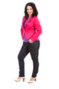 Casual woman in pink jacket brunette standing with hands pockets jeans semi profile isolated on white background Stock Photo