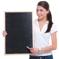 Casual woman presents on blackboard young presenting with a piece of chalk a while smiling to the camera isolated white background Stock Image