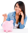 Casual woman saving money in a piggybank isolated over white background Stock Photography