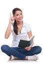 Casual woman sits reads has idea young sitting with legs crossed and having an while holding a book pointing up while looking at Royalty Free Stock Photography