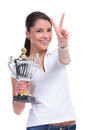 Casual woman with trophy victory young holding a and showing the sign while smiling to the camera isolated on white background Stock Photos