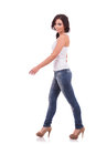 Casual woman walking full length of a young to the side and looking at the camera with a smile on white background Royalty Free Stock Image