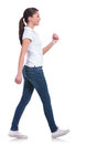 Casual woman walking side view of a young away from the camera and smiling isolated on white background Royalty Free Stock Photos