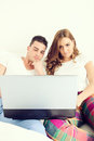 Casual young couple enjoying using laptop computer in bed for the internet and watching movies Stock Photos