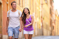 Casual young couple holding hands walking in rome italy europe multiracial in love having fun laughing together asian woman Royalty Free Stock Photography