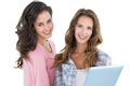 Casual young female friends with digital tablet portrait of two against white background Stock Photo
