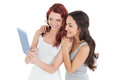 Casual young female friends looking at digital tablet two against white background Royalty Free Stock Images