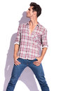 Casual young man holding his thumbs in his pockets with his legs spread and looking up and to a side away from the camera isolated Stock Photos