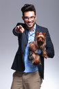 Casual young man holds puppy and points at you holding a pointing the camera with a smile on his face on gray background Stock Image