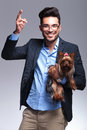 Casual young man holds puppy and shoots with hand holding a making a shooting gesture his while smiling for the camera on gray Stock Image
