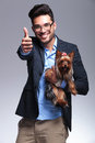Casual young man holds puppy and shows thumb up holding a showing the thumbs gesture to the camera with a smile on his face on Stock Photography