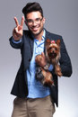 Casual young man holds puppy and shows victory Royalty Free Stock Photo