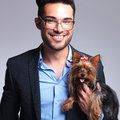 Casual young man holds puppy and smiles Royalty Free Stock Photo