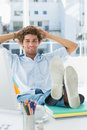 Casual young man with legs on desk in bright office Royalty Free Stock Photography