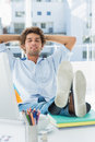 Casual young man with legs on desk in bright office Royalty Free Stock Images