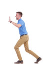 Casual young man pushes something imaginary full length side view picture of a pushing with great difficulty isolated on a white Stock Photography