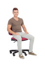 Casual young man sitting on an office chair isolated a white background Stock Image