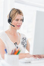 Casual young woman with headset using computer in a bright office Stock Images