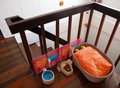 Cat bed soft orange pillow in a basket as kitten in a vintage style home with wooden floor and staircase with food and water Stock Photography