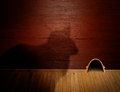 Cat and mouse a shadow of a patient staring at a hole in a red textured wall on a wooden floor Stock Images