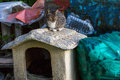 Cat sits on dog house.