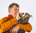 Cat trying to catch the glasses of a man cute Royalty Free Stock Photography