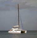 A catamaran motoring into the shelter of admiralty bay bequia yacht seeking calm anchorage before arrival tropical storm Royalty Free Stock Photo