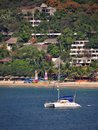Catamaran in zihuatanejo this is an image of a the bay of the background people can be seen relaxing and enjoying la ropa beach Stock Photo