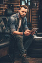 Catching up some hairstyles online handsome young bearded man holding digital tablet and looking at camera while sitting in Royalty Free Stock Images