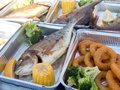 Catering portions of small fish and other seafood served with boiled vegetables Royalty Free Stock Photo