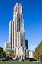 Cathedral of learning towers over green and yellow trees against a deep blue sky in oakland a sub city pittsburgh pennsylvania Stock Images