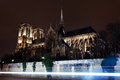 Cathedral notre dame de paris and seine river traffic at night Royalty Free Stock Images