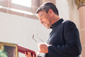 Catholic priest reading bible in church Stock Images