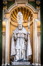 Catholic priest statue of nice cathedral detail facade in close up view with staff in hand under yellow arch sculpture as Stock Image