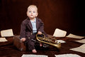 Caucasian baby boy plays with trumpet between sheets musical notes against brown background Stock Image