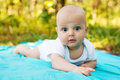 Caucasian baby boy takes rest at blue towel in summer park Stock Images