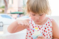 Caucasian baby girl eats frozen yogurt close up outdoor portrait with natural light Royalty Free Stock Images