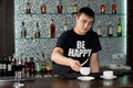 Caucasian barman serving coffee at the bar young wearing a funny t shirt with an optimistic message with shelves with bottles of Royalty Free Stock Photos