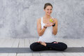 Caucasian beautiful healthy athletic sportive girl eat green apple after the training and looking at camera Royalty Free Stock Photo