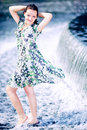 Caucasian beautiful teen girl with dark hair and blue eyes is standing in the flowing water near a waterfall. Looking at camera an