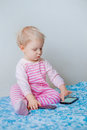 Caucasian blond baby making a call, playing with mobile cell phone with funny expression on face Royalty Free Stock Photo