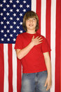 Caucasian boy with hand over heart with american flag background Royalty Free Stock Photo