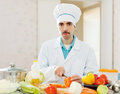 Caucasian cook does veggy lunch at kitchen in white uniform Stock Image