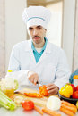 Caucasian cook does veggy lunch in uniform Stock Photo