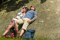 Caucasian couple enjoying sunshine on rock resting backpack Stock Photography